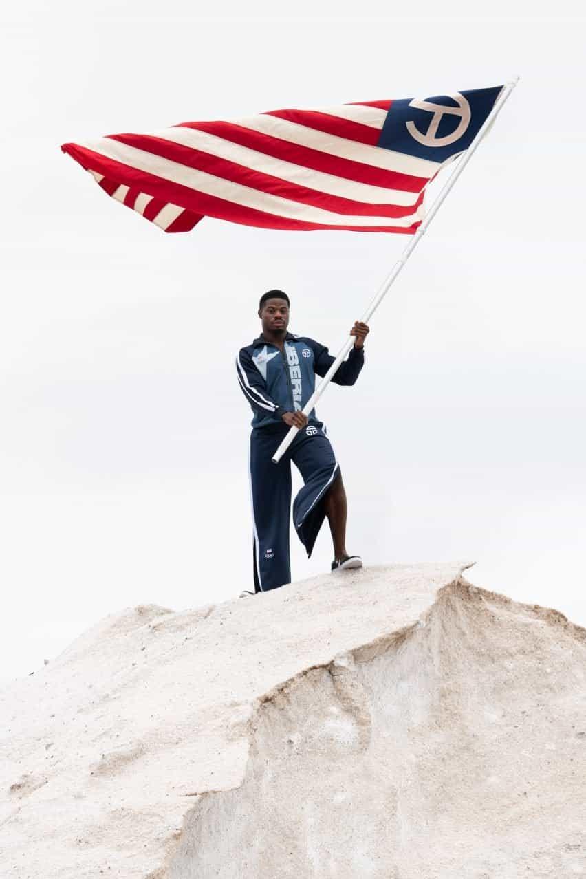 Un hombre ondea una bandera vistiendo el uniforme olímpico de Telfar
