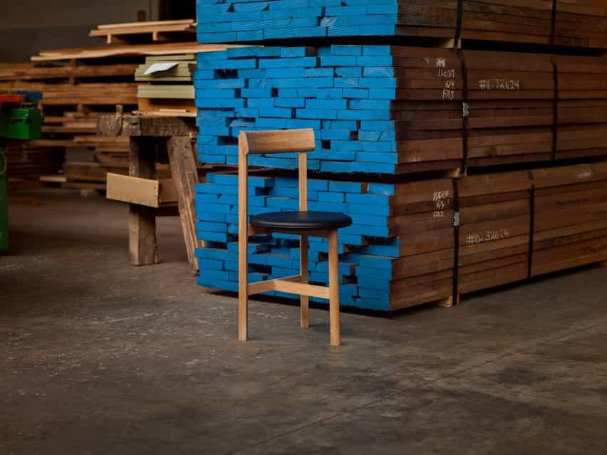 Tiene un asiento de cuero y un marco de madera de Neri&Hu