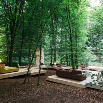 Prostoria anida pabellón de madera llena de frondosos árboles en el bosque de Croacia
