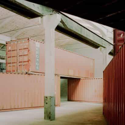 Amaa pilas de contenedores de transporte en la fábrica italiana para crear un espacio dentro de un espacio