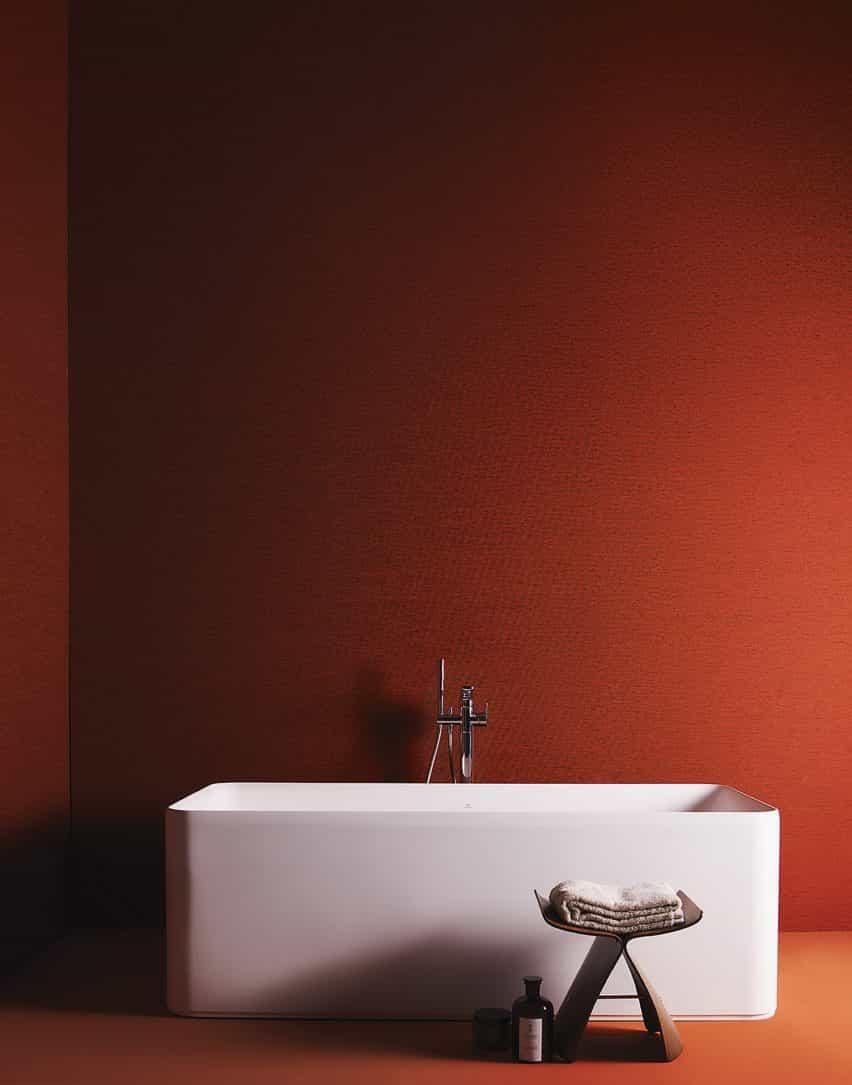 Un baño de color naranja cálido con bañera blanca independiente