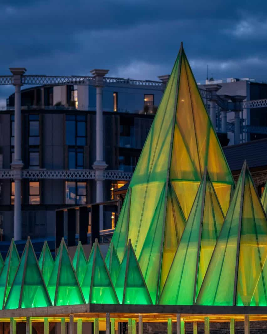 Cerca de la instalación eléctrica de la Navidad de Nemeton por Sam Jacob Studio en King's Cross, Londres, por la noche