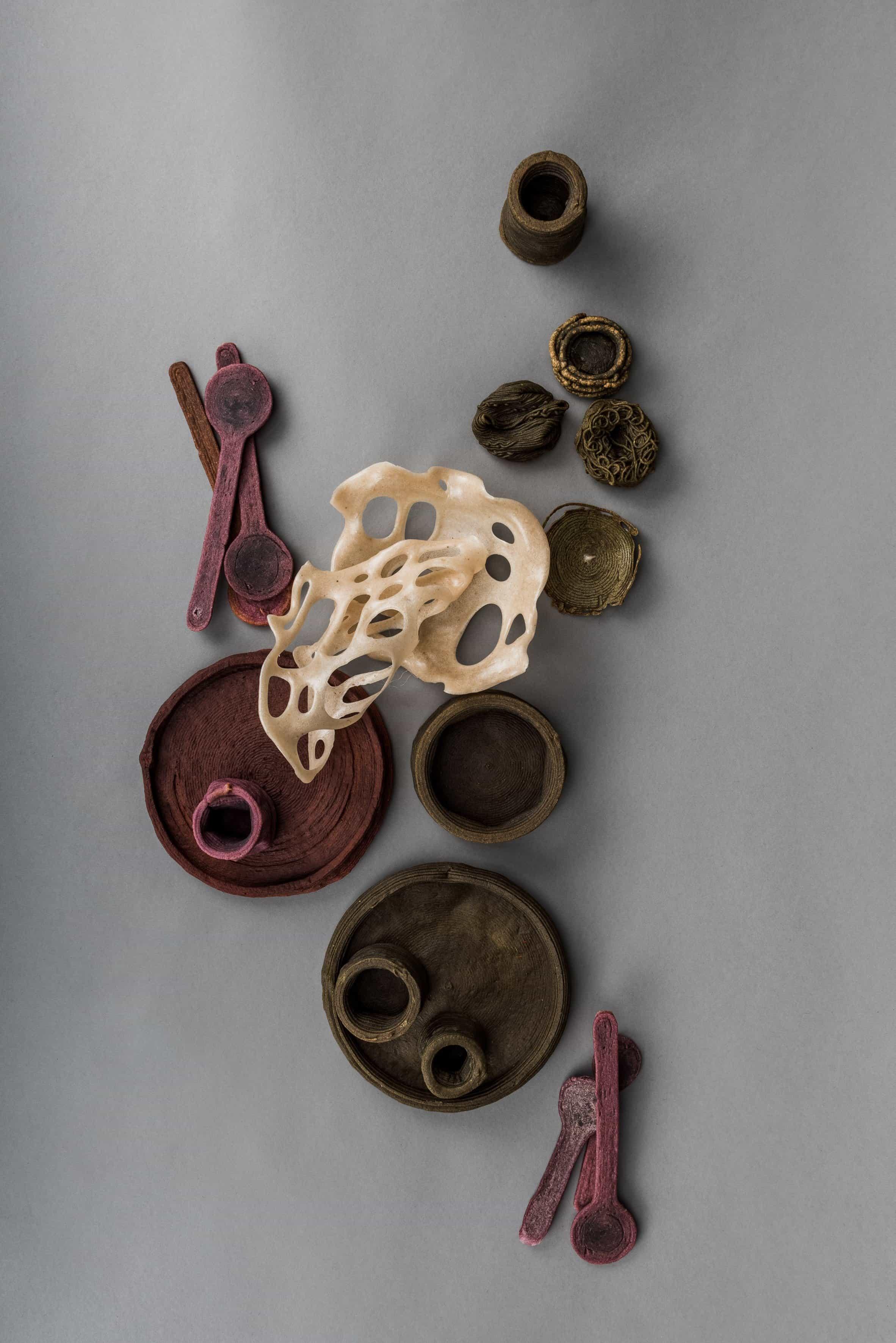 Platos, cuencos y cubiertos de desechos dispuestos sobre una superficie gris