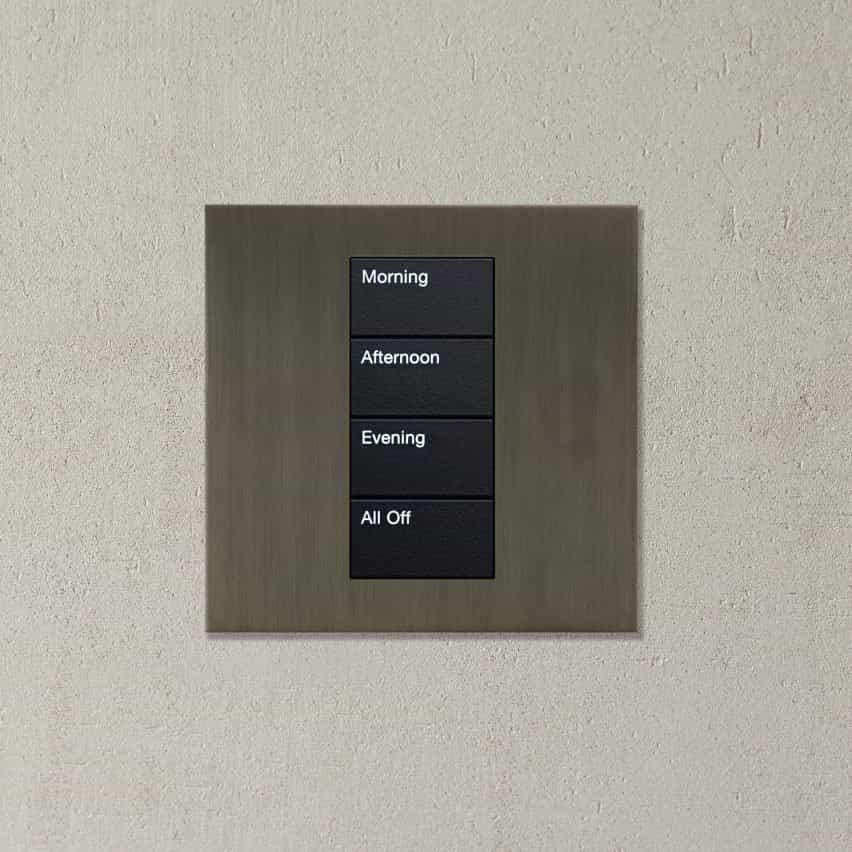 Un control de iluminación metálico con cuatro interruptores: mañana, tarde, noche y todo apagado