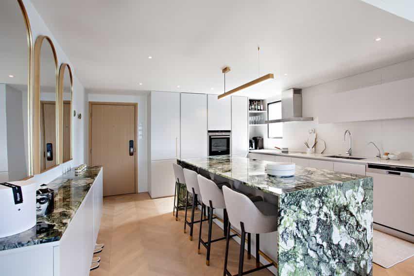 Mesa de cocina de mármol verde en cocina blanca