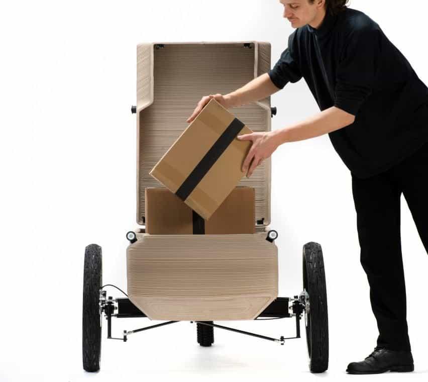 Hombre poniendo una caja en el compartimiento de almacenamiento de un triciclo eléctrico por EOOS NEXT