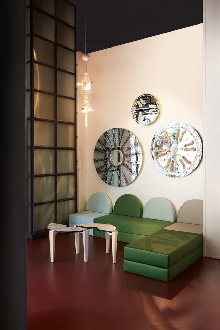 Sofá verde bajo espejos circulares.