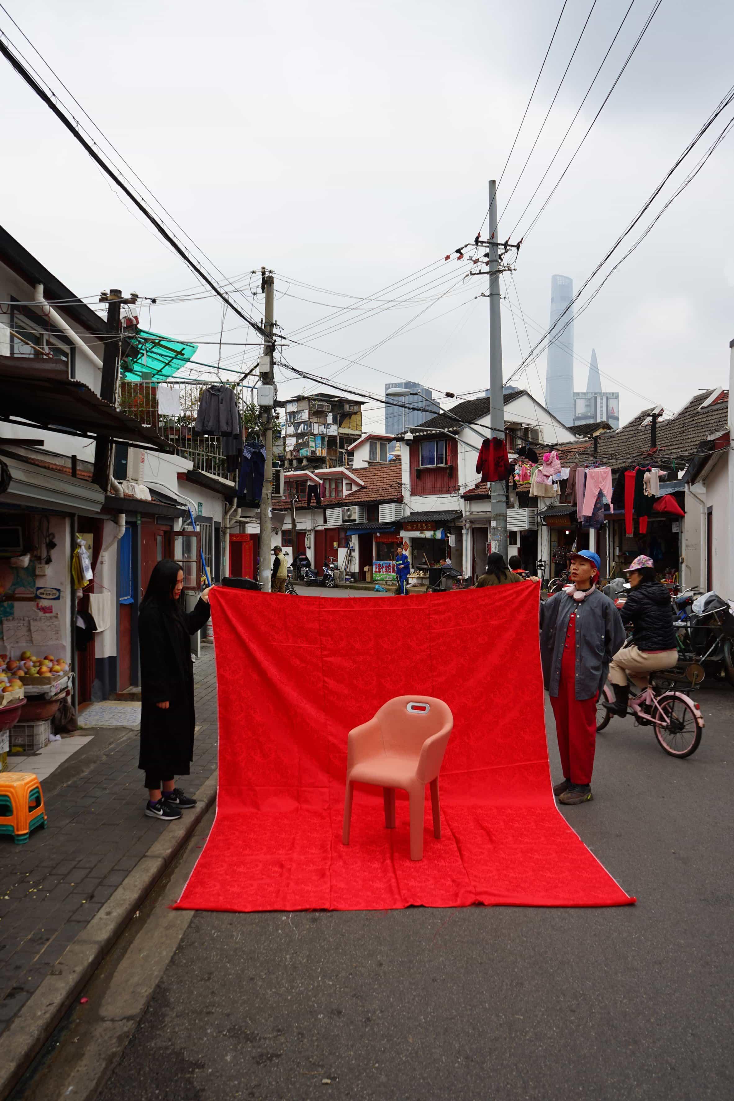 Silla fotografiada contra una sábana roja sostenida por dos lugareños en una calle china