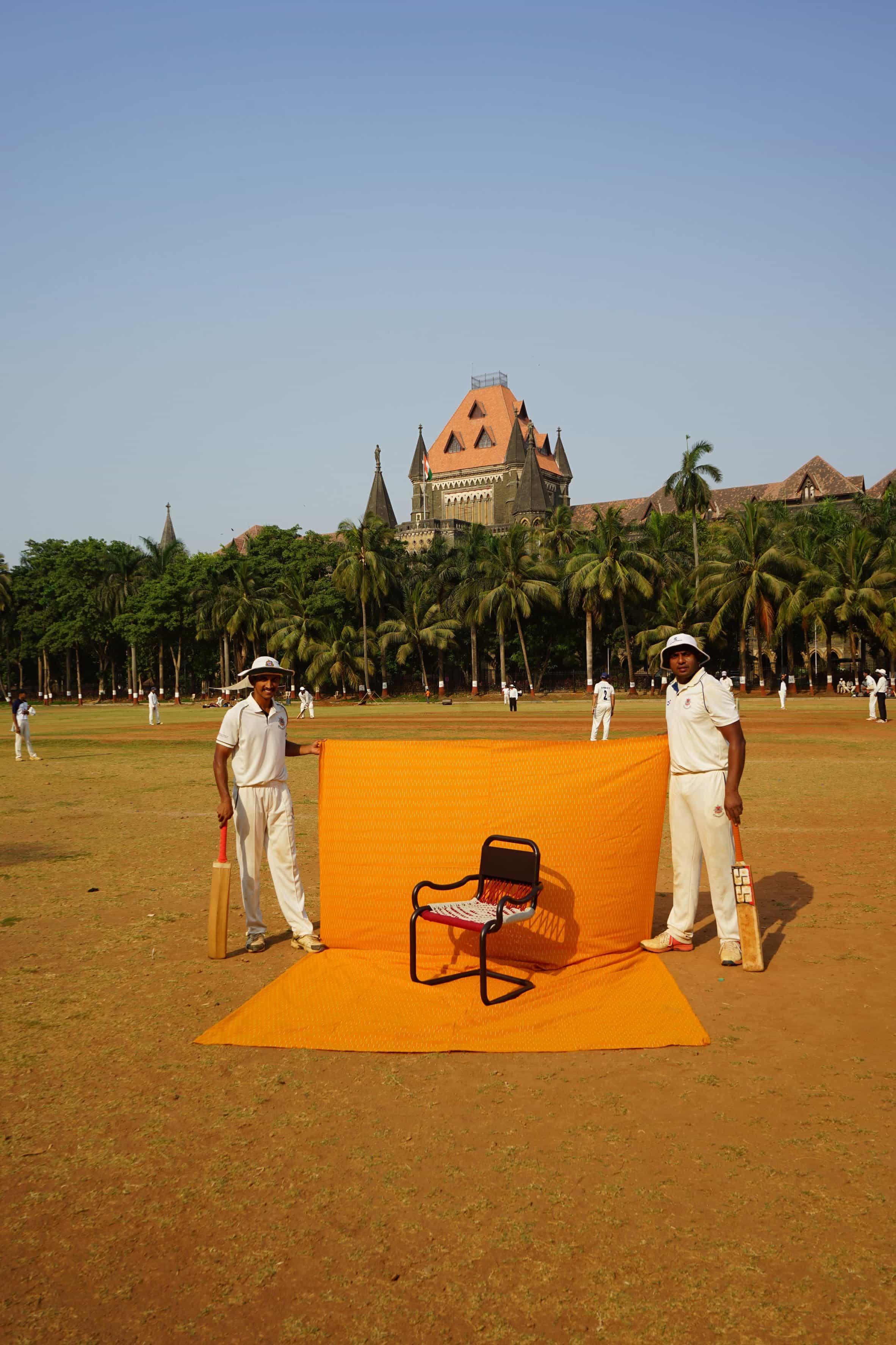 Silla fotografiada contra una sábana amarilla sostenida por dos jugadores de cricket en un campo de cricket en la India