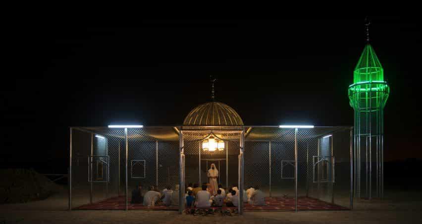 La gente se reúne dentro de la mezquita de acero por la noche