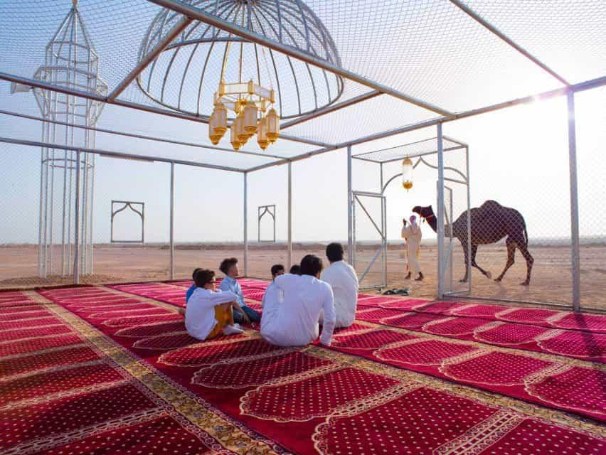Un grupo de personas se sienta bajo la cúpula de la mezquita de alambre, mirando a un camello que pasa.