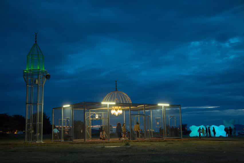 La instalación de la mezquita de acero al atardecer, con el minarete iluminado en verde