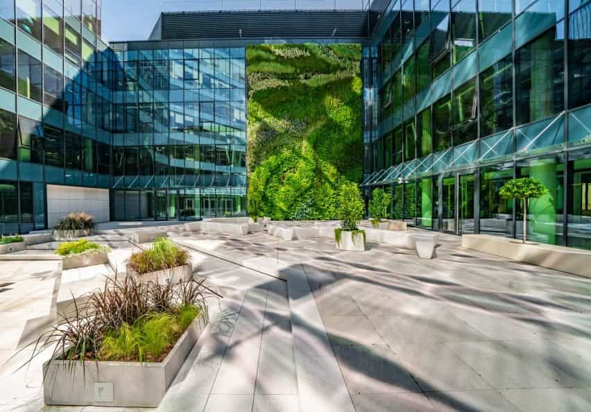 Una fotografía de un edificio de cristal con pared verde.