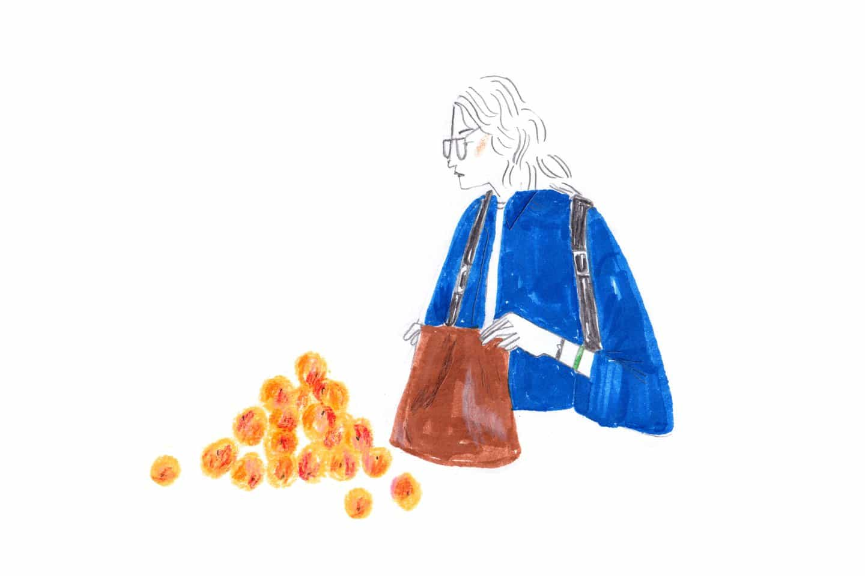 Una señora recogiendo melocotones en el mercado de la ciudad