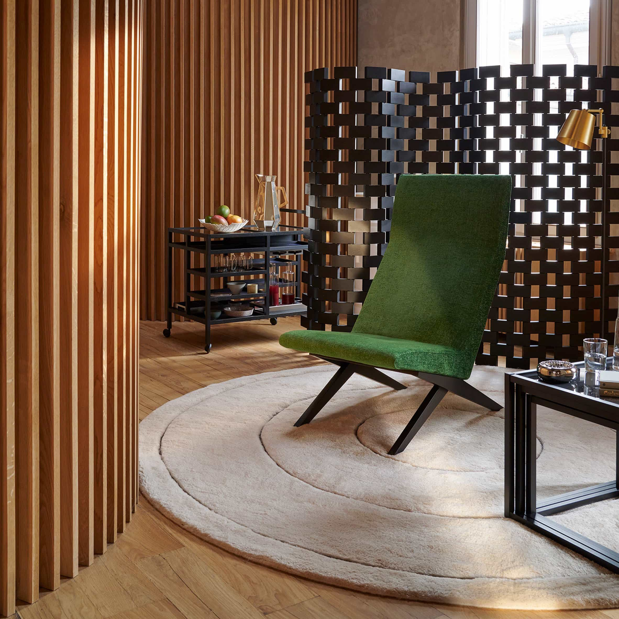 Pantalla Paravent Ambassade de Charlotte Perriand detrás de una silla verde