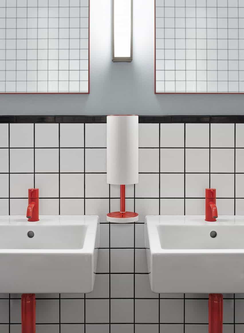 Dispensador RS11 rojo y blanco montado en la pared entre lavabos en un baño público