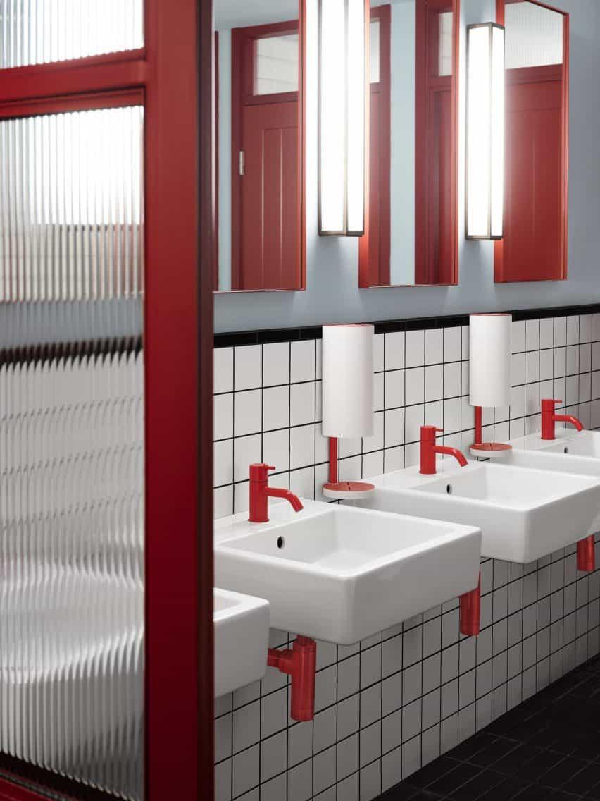 Dispensadores RS11 de pared rojos y blancos instalados dentro de un baño