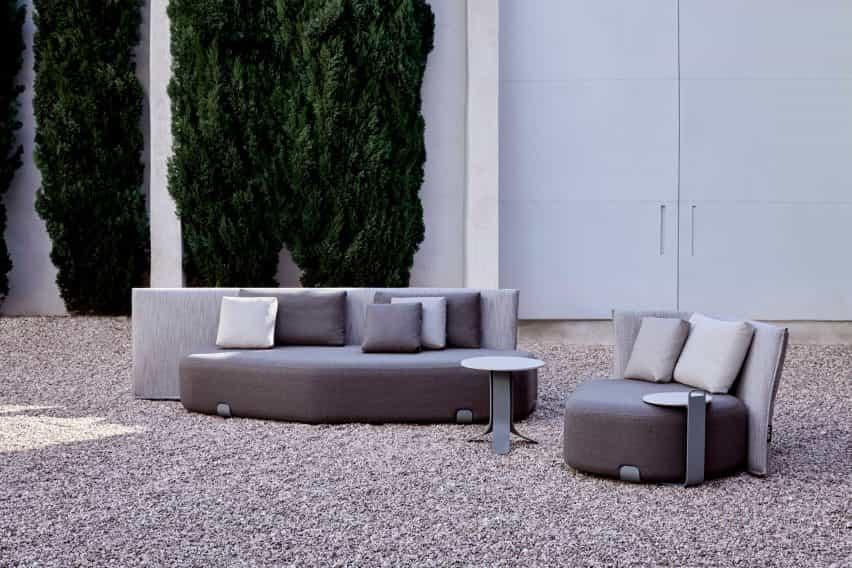 Hay un asiento al aire libre tapizado gris por Gan